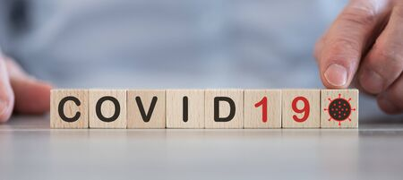 Concept of Covid-19 on wooden cubes