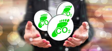 Carbon footprint concept above the hands of a woman in background