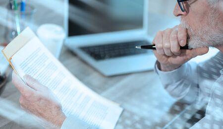 Uomo d'affari che controlla un documento in ufficio; effetto luce