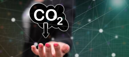 Carbon reduction concept above the hand of a woman in background