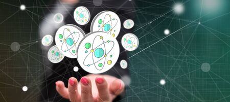 Nuclear research concept above the hand of a woman in background