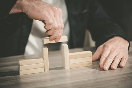 Male hand building a bridge with wooden blocks; concept of association Archivio Fotografico