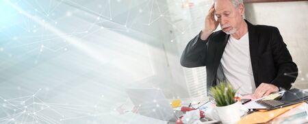 Overworked senior businessman sitting at a messy desk; panoramic banner Reklamní fotografie