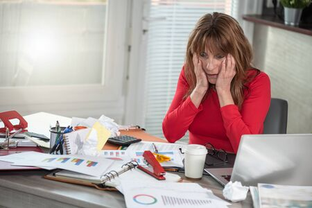 Overworked mature businesswoman sitting at a messy desk Banque d'images