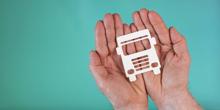 Concept of truck insurance with paper truck in hands on turquoise color background