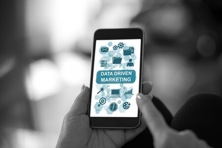 Hand holding a smartphone with data driven marketing concept