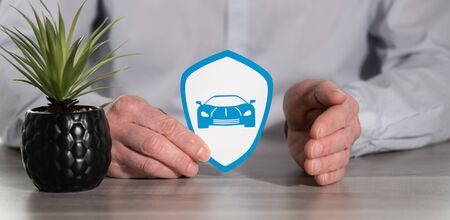 Concept of sports car insurance with paper shield protected by hand of insurer 版權商用圖片