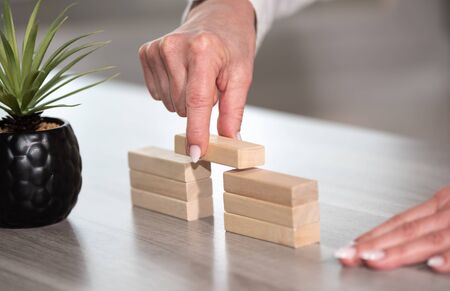 Female hand building a bridge with wooden blocks; concept of association