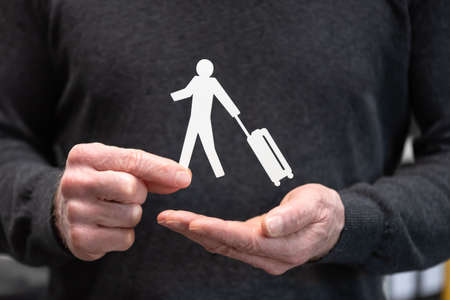 Man holding a paper traveller; Concept of travel insurance