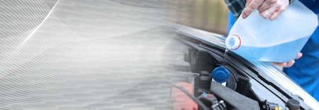Hands of mechanic pouring blue windshield washer fluid in a car; panoramic banner Reklamní fotografie