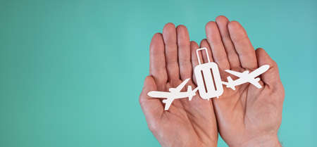 Concept of baggage insurance with paper planes and suitcase in hands on turquoise color background Archivio Fotografico