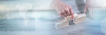 Female hand building a bridge with wooden blocks; concept of association; panoramic banner