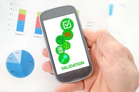 Validation concept on a smartphone held by a hand
