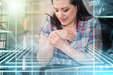 Young businesswoman suffering from wrist pain; multiple exposure Foto de archivo