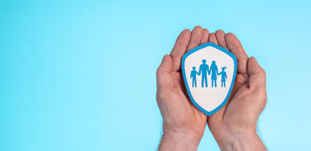 Concept of family insurance with paper shield in hands on blue background