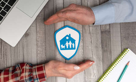 Concept of family and house insurance with hands in a protective gesture Stockfoto