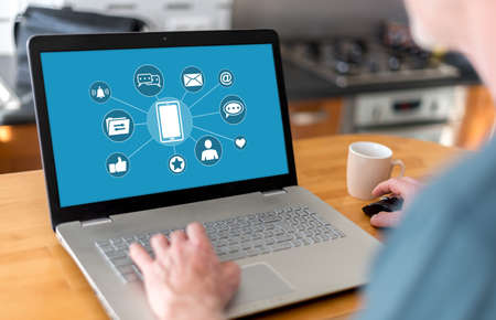 Man using a laptop with mobile apps concept on the screen Stock fotó