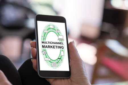 Hand holding a smartphone with multichannel marketing concept