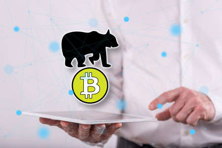 Bitcoin bearish trend concept above a tablet held by a man in background