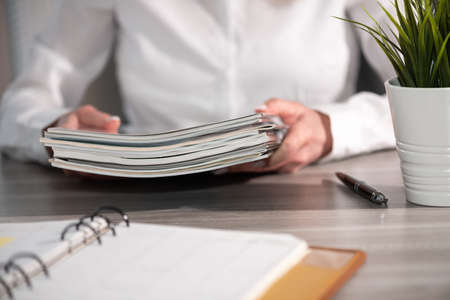 Female hands holding a stack of magazines