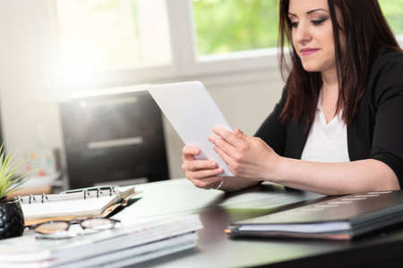 Businesswoman using digital tablet at workplace Banque d'images
