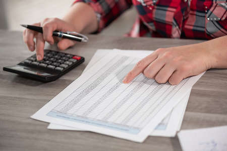 Woman using calculator and working on financial data Stock fotó