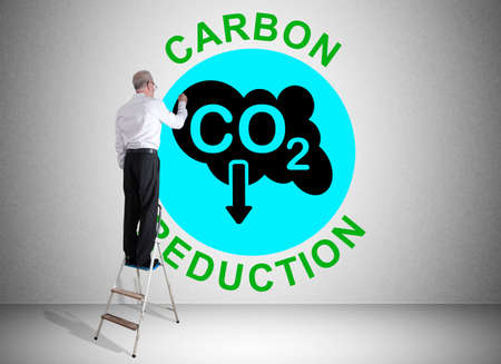 Man on a ladder drawing carbon reduction concept on a wall