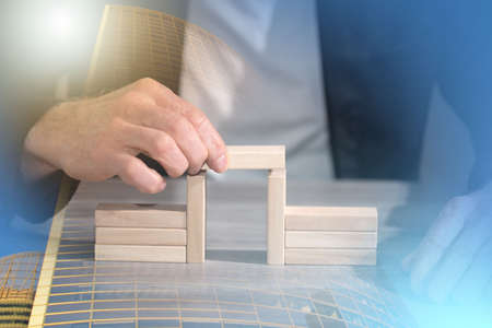 Male hand building a bridge with wooden blocks; concept of association; multiple exposure