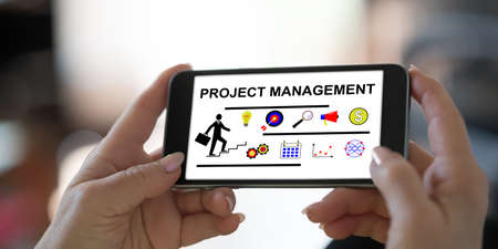 Hand holding a smartphone with project management concept Banco de Imagens