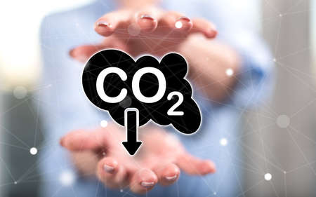 Carbon reduction concept between hands of a woman in background