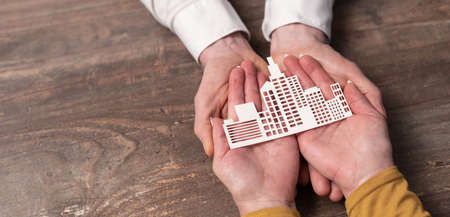 Concept of business insurance with paper building in hands