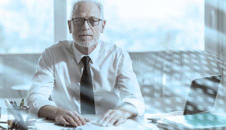 Portrait of mature businessman sitting in office; light effect
