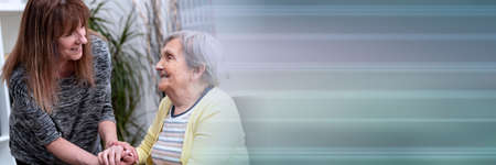 Portrait of old mother supported by her daughter; panoramic banner