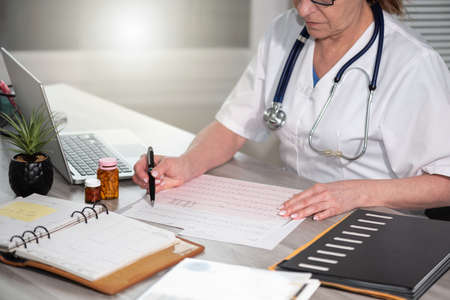 Female cardiologist examining an ecg graph in medical office Archivio Fotografico