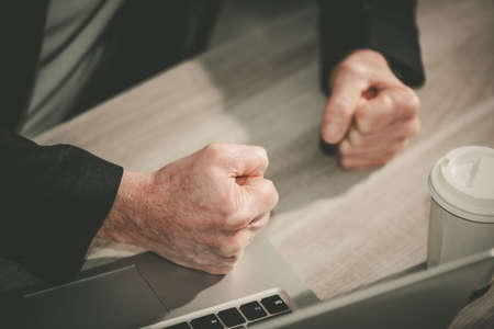 Angry businessman hitting his desk with his clenched fists Stock Photo