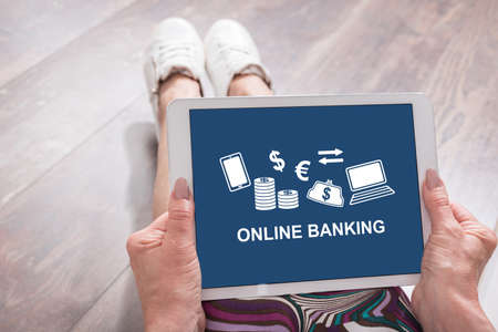 Woman sitting on the floor with a tablet showing online banking concept Foto de archivo
