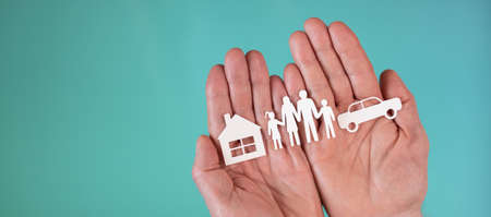 Concept of life, auto and home insurance with paper family, car and house in hands on turquoise color background