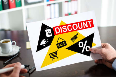 Hand holding a paper showing discount concept