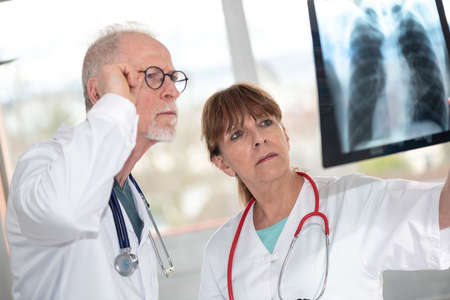 Two doctors examining x-ray report in medical office 写真素材