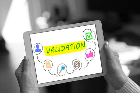 Validation concept shown on a tablet held by a woman
