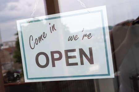 Come in we're open sign hanging behind a store window