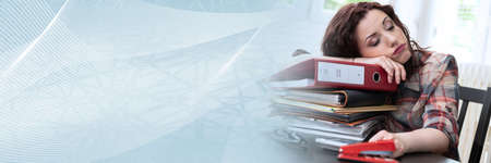 Exhausted businesswoman with a stack of folders on her desk; panoramic banner