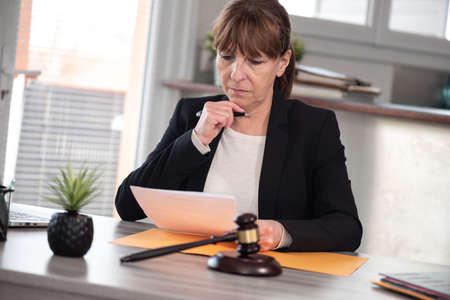 Female lawyer working on document. Legal, advice and justice concept