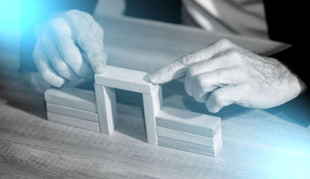 Male hand building a bridge with wooden blocks; concept of association; light effect