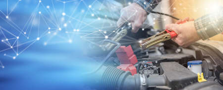 Hands of car mechanic using cables to start a car engine; panoramic banner