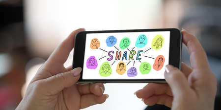 Hand holding a smartphone with share concept Stock Photo