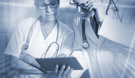 Two mature doctors discussing about medical report on tablet; light effect