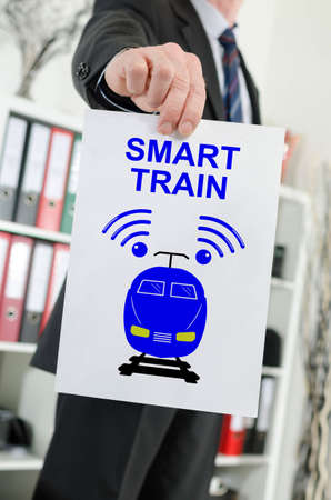 Paper showing smart train concept held by a businessman