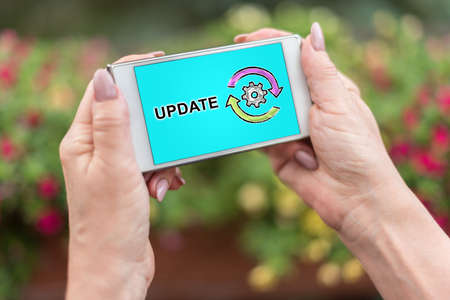 Female hands holding a smartphone with update concept Stock Photo