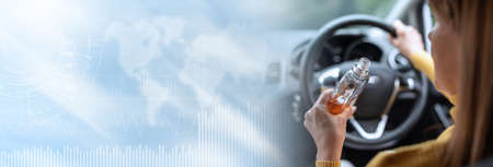 Woman drinking alcohol while driving; panoramic banner